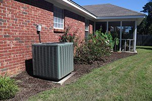 Air Conditioner system next to a home, modern clean with bushes and brick wall